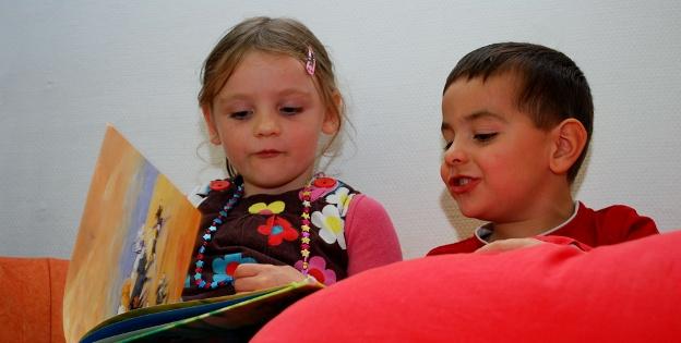 ein kleines Mädchen und eine kleiner Junge sitzen auf einem Sofa und schauen gemeinsam ein Bilderbuch an