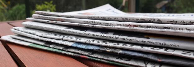 Ein Zeitungsstapel liegt auf einem Tisch