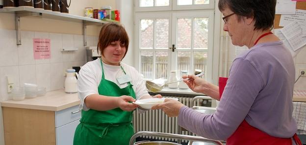 In einer Küche schöpft eine Frau Suppe auf einen Teller, der von Simone Leutner gehalten wird