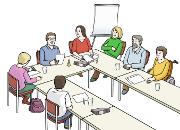 7 Menschen sitzen in einem Arbeitsraum an Tischen und reden miteinander