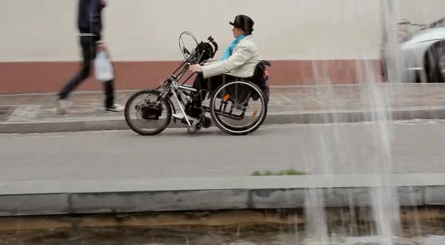 Eine Rollifahrerin rollt an einem Brunnen vorbei